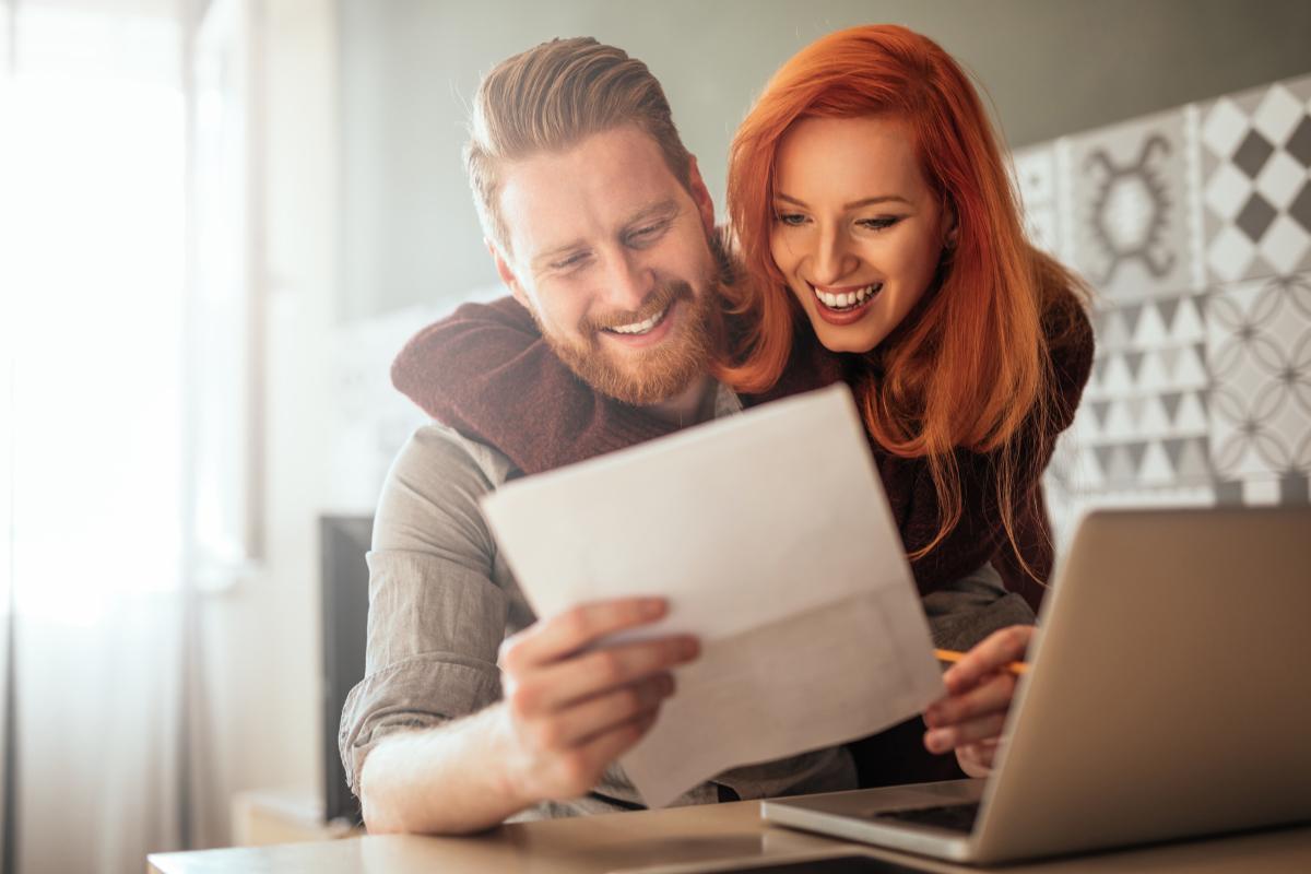 Crédits immobiliers à Toulouse - Un couple heureux lit un document