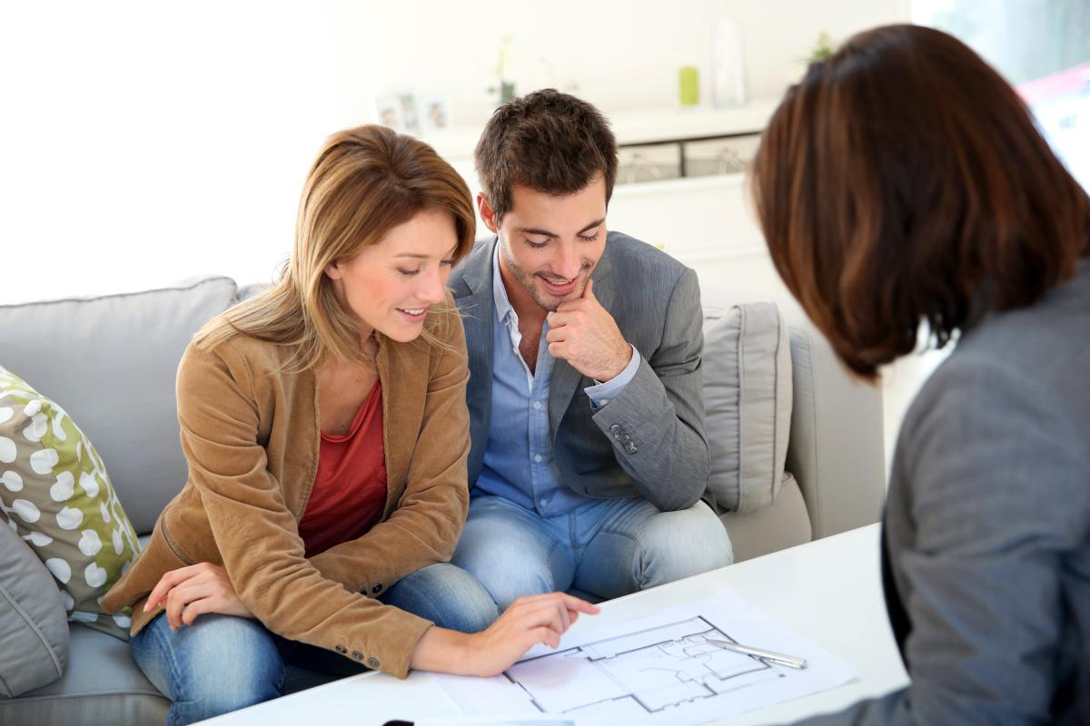 Aide achat immobilier - Un couple propriétaire en rendez-vous chez un architecte pour étudier les travaux à effectuer au sein de leur logement