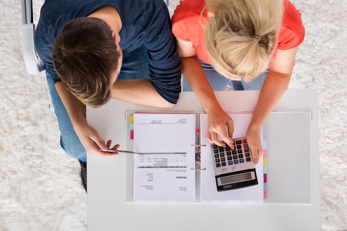 Aide premier achat immobilier - Un couple calculant les aides telles que APL auxquels ils ont droit