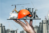 Dessine-moi Toulouse – Main qui tient une tablette numérique sur laquelle est posé des symboles de la construction immobilière.