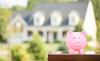 Défiscalisation immobilière à Toulouse - Tire-lire cochon avec une maison en arrière plan.