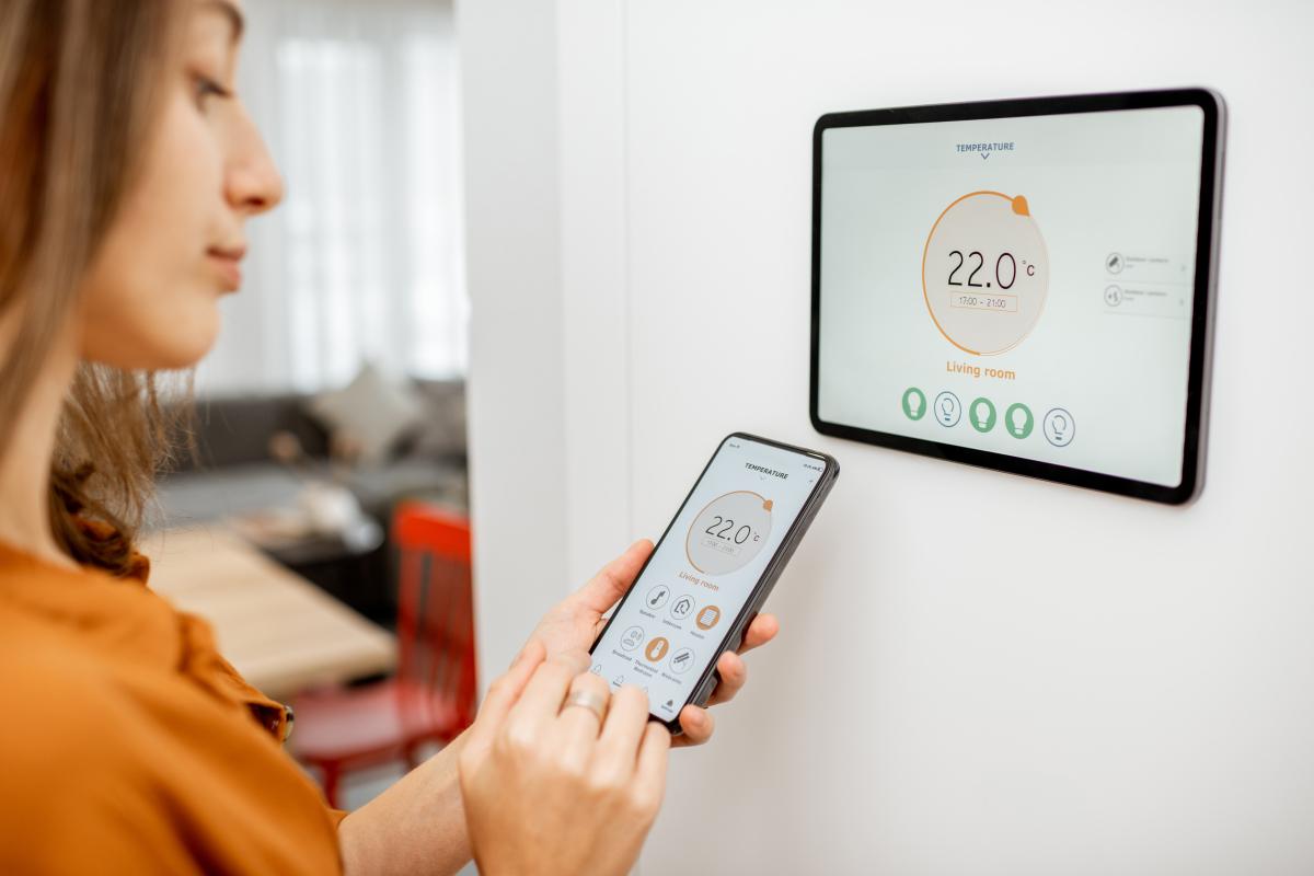 Maison neuve à Toulouse – Femme qui utilise son système domotique pour le chauffage