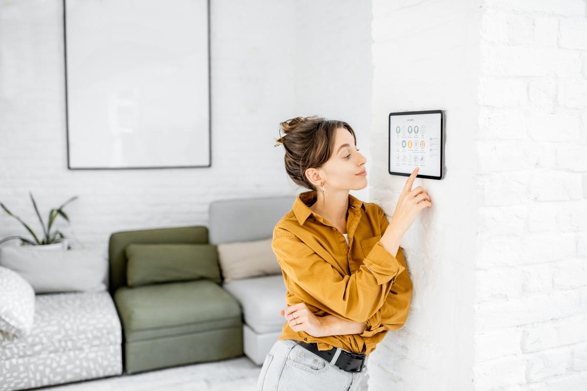objet connecté  –  femme pilotant son logement connecté depuis une tablette