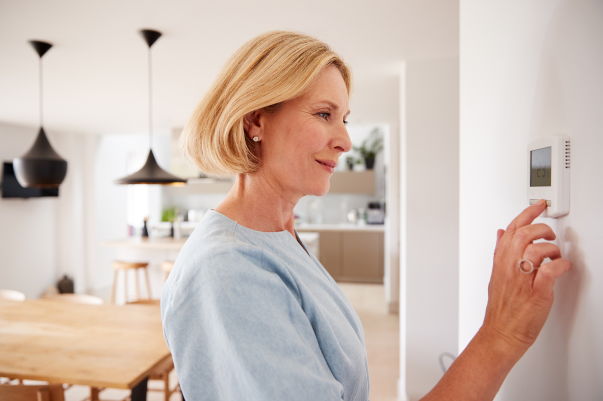 objet connecté  –  femme allumant l'alarme connectée de son logement depuis une commande centralisée
