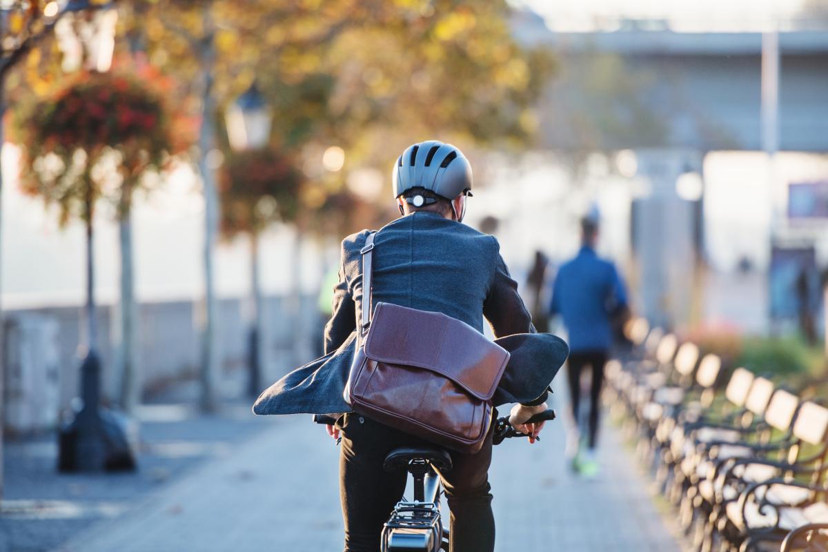Homme avec une sacoche circulant en vélo dans une ville