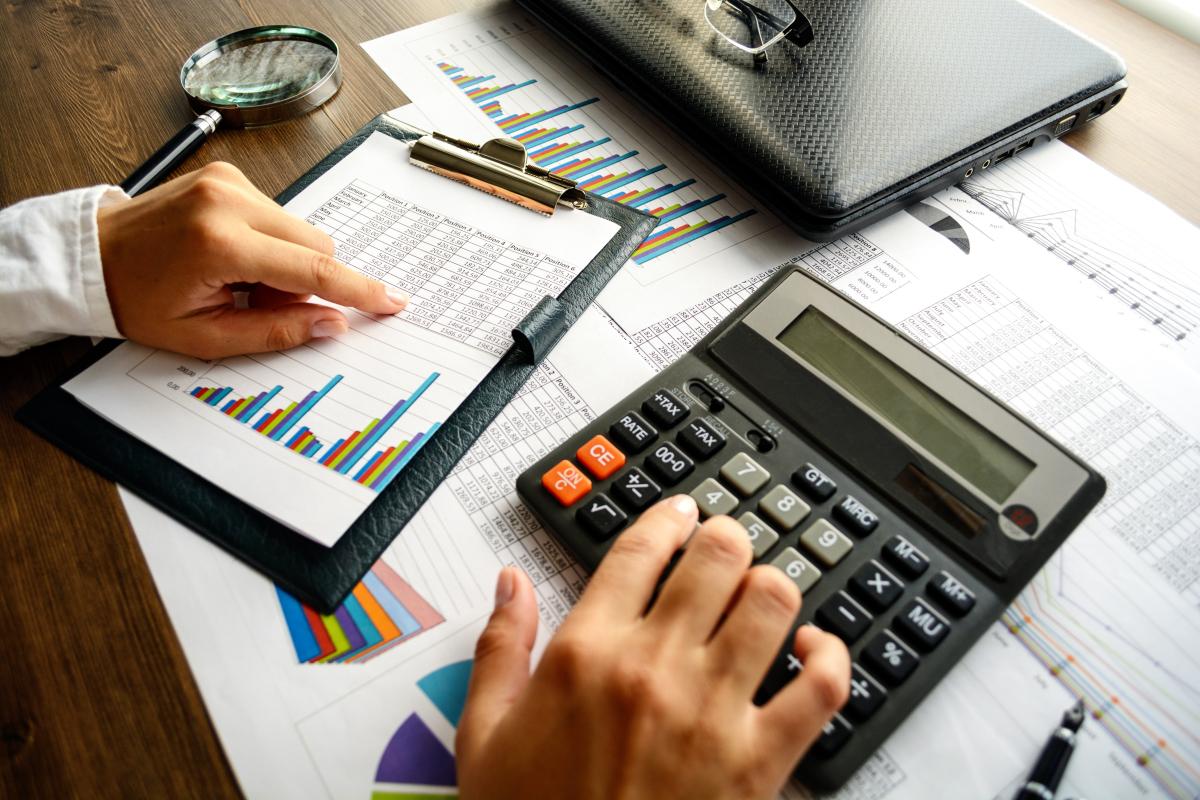 Mains d'un homme faisant des calculs avec calculatrice tableau de comptes et graphique