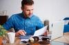 Un homme en train de calculer ses dépenses et recettes à l'aide d'un ordinateur et d'une calculatrice