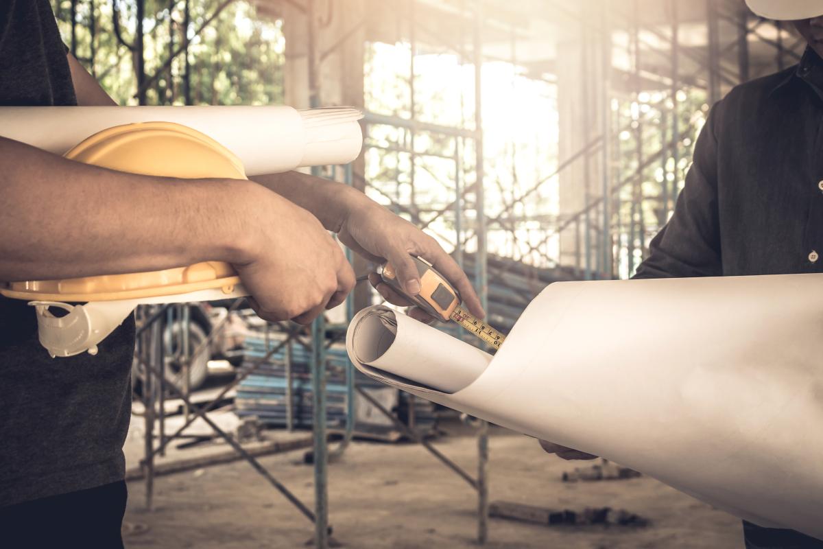 Deux ouvriers sur un chantier à Toulouse en train d'échanger des plans