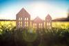 Aides à la transition énergétique – Figurines en bois d'immeubles et d'une maison dans l'herbe