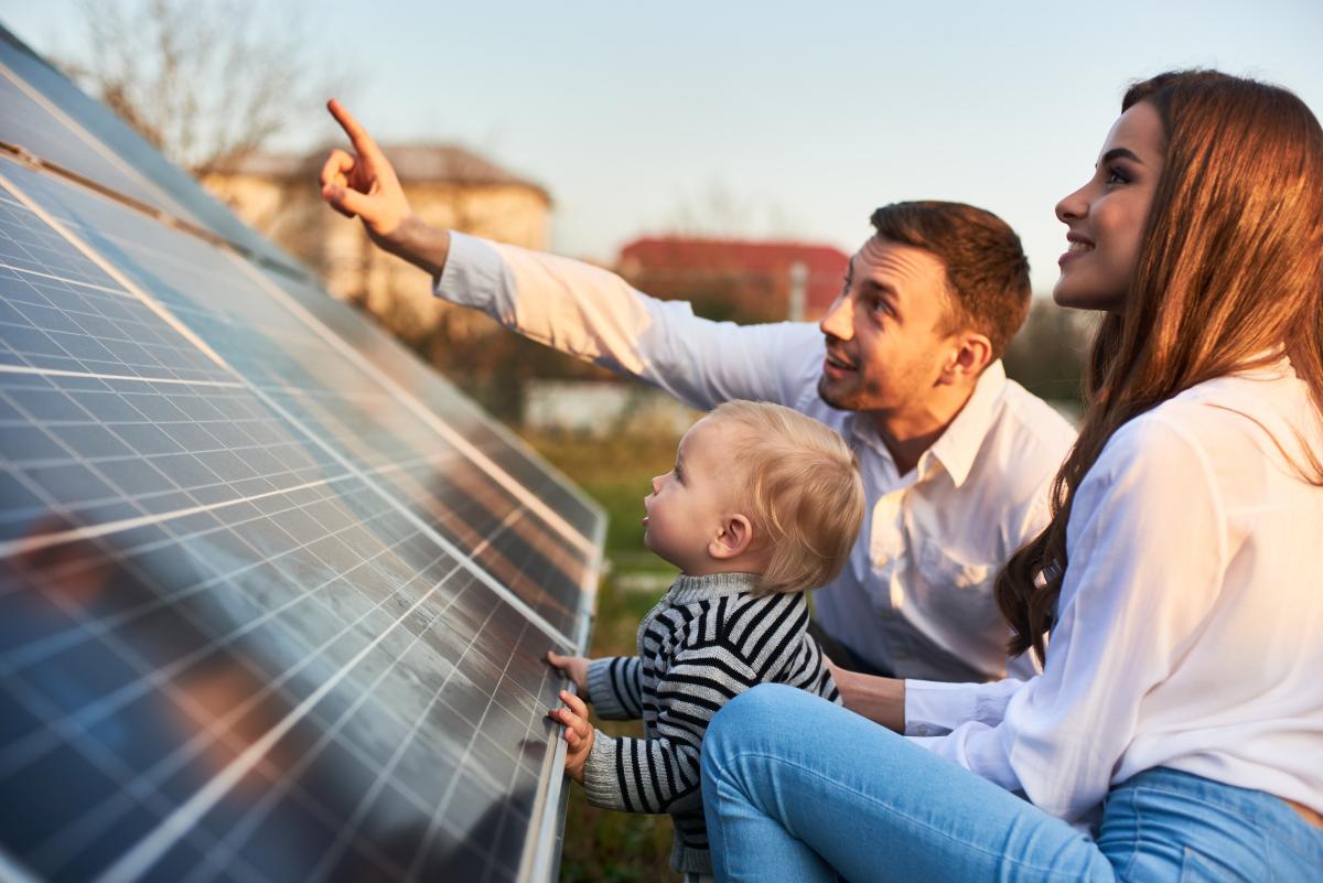 Aides à la transition énergétique – Des parents et leur enfant près d'un panneau solaire