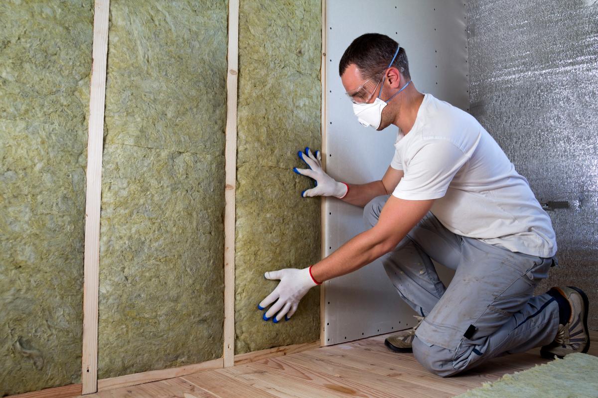 Un homme pose de l'isolant sur les murs dans un immeuble