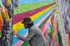 QPV à Toulouse – Homme réalisant une fresque murale colorée dans une rue