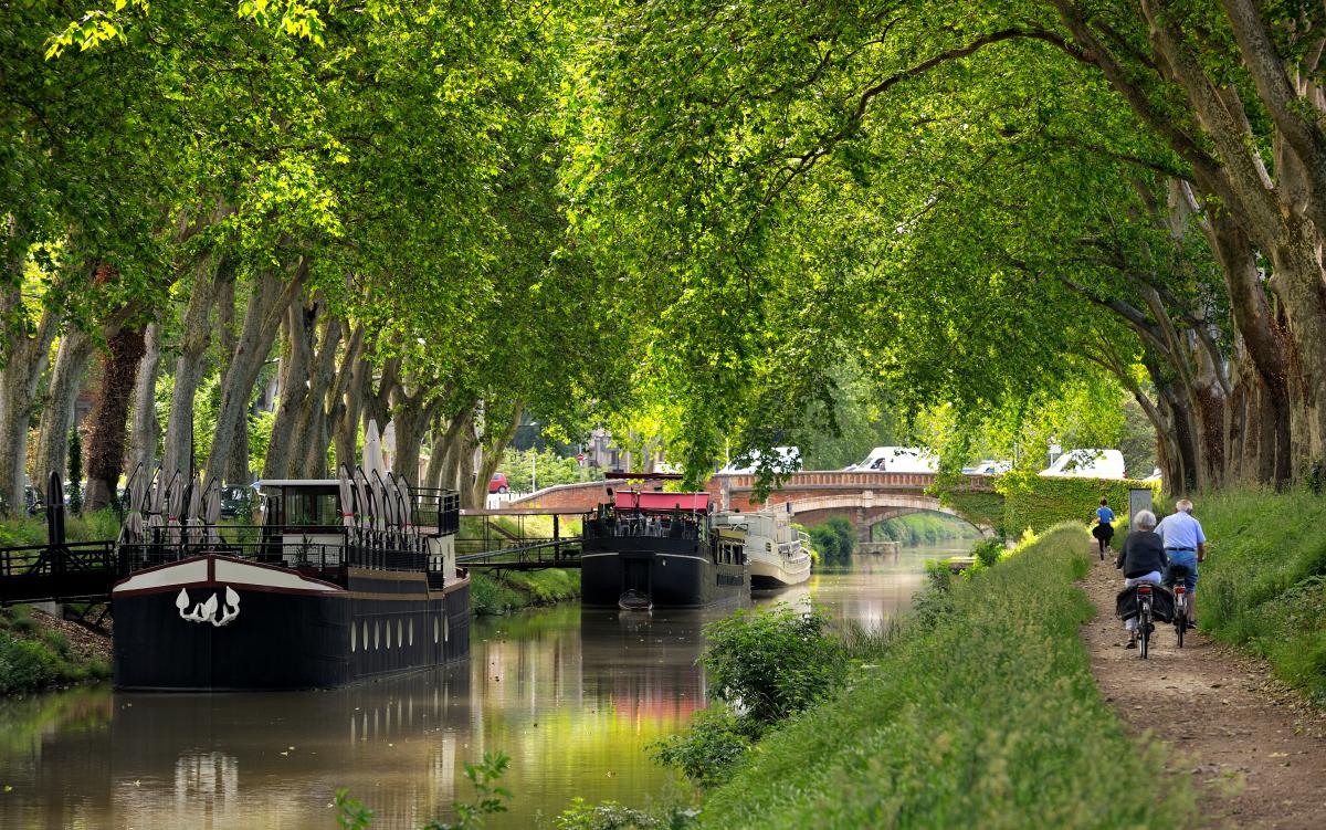 VNF Canal du Midi – Promeneurs le long du Canal du Midi et péniches naviguant